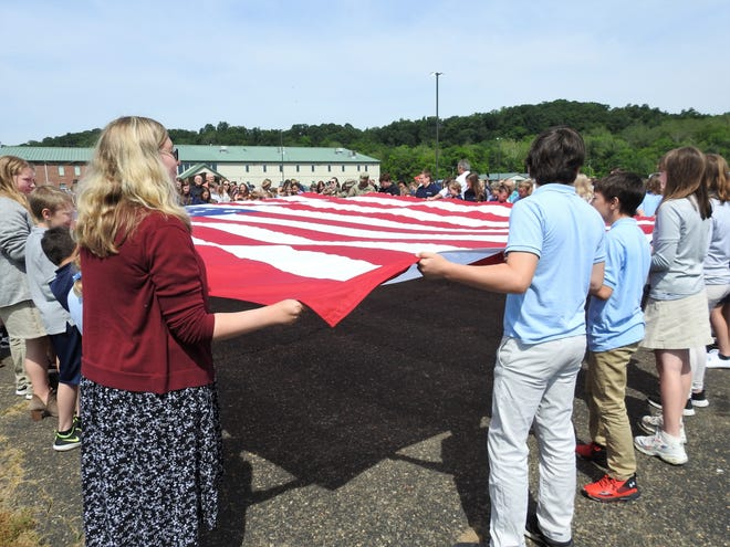 Staff and students hold a U.S. Flag for attachment and running up a 72-foot flagpole recently moved about 400 feet to the edge of the parking lot at Coshocton Christian Tabernacle.