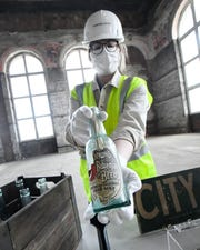 Ford Archives and Heritage team member Lauren Dreger shows a Stroh's beer bottle with a message in it that was found behind the walls at the Michigan Central train station as restoration work continues by Ford Motor Company.