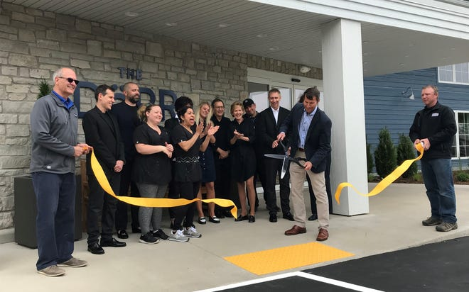 Chris Schmeltz, owner and developer of the Dorr Hotel in Sister Bay, cuts the ribbon during a May 27 ceremony to open it to the public.