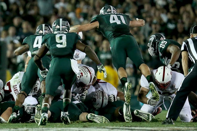 Kyler Elsworth dives into the pile to help stop Stanford in the final moments of the Rose Bowl on Jan. 1. Several Spartan greats compared it to another No. 41, Charlie Thornhill, from the 1960s.