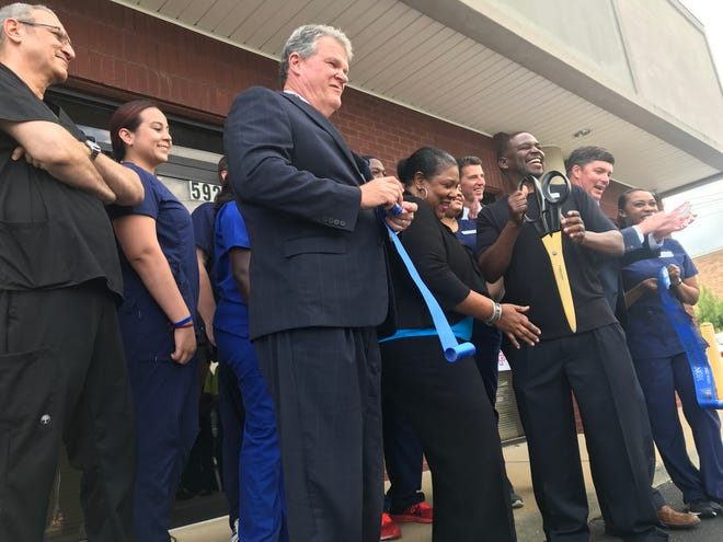 Dr. Donovan Harper cuts a ribbon at his new Federal Injury Center clinic in Montgomery alongside staff members and local officials.