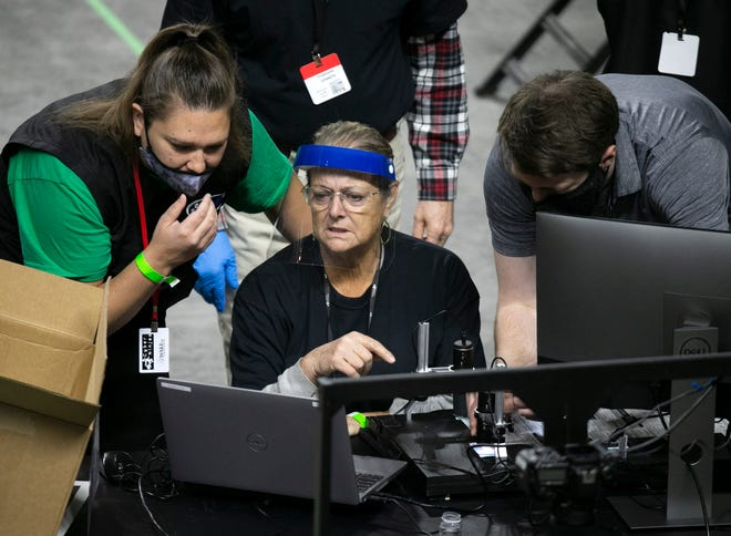 Maricopa County ballots from the 2020 general election are examined and recounted by contractors hired by the Arizona Senate in an audit at the Veterans Memorial Coliseum in Phoenix on May 27, 2021.