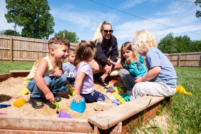 Maddie Mead, center, plays in the sandbox with a group of kids Thursday, May 27, 2021, at Miss Maddie's Daycare in China Township.