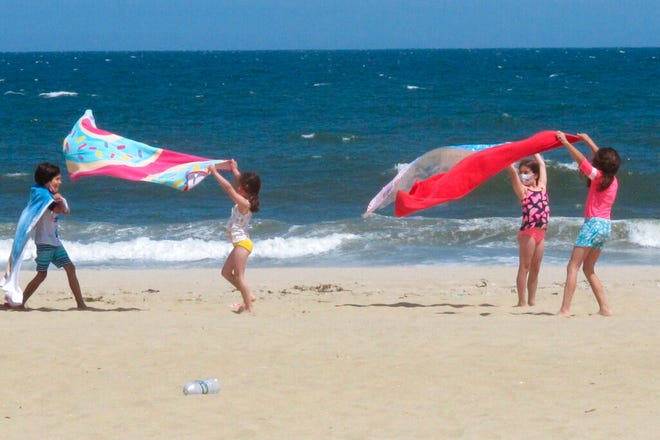 Children play with beach towels on a windy day in Belmar N.J. on Tuesday, May 25, 2021. Businesses and residents alike expect this summer at the Jersey Shore to be busier than last year as more people get vaccinated and COVID19 restrictions are scaled back or eliminated. (AP Photo/Wayne Parry)