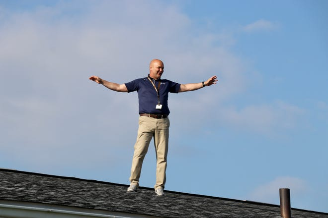 Christian School of York Superintendent Andy Bell greets students as they arrive to school on Thursday, May 27, 2021. Bell spent the night camped out on the school's roof as part of a fundraiser incentive. Tina Locurto photo.