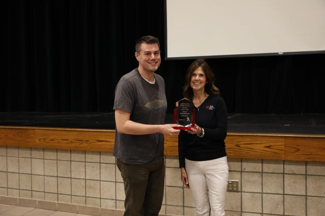 Michelle Bunkers (right) from First National Bank presents Robert Michalscheck with the Dell Rapids Teacher of the Year award.