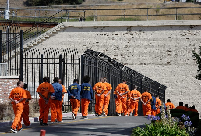 FILE - In this Aug. 16, 2016, file photo, a row of general population inmates walk in a line at San Quentin State Prison in San Quentin, Calif. Three-quarters of California's district attorneys sued the state Wednesday, May 26, 2021, in an attempt to block emergency rules that expand good conduct credits and could eventually bring earlier releases for tens of thousands of inmates. (AP Photo/Eric Risberg, File)