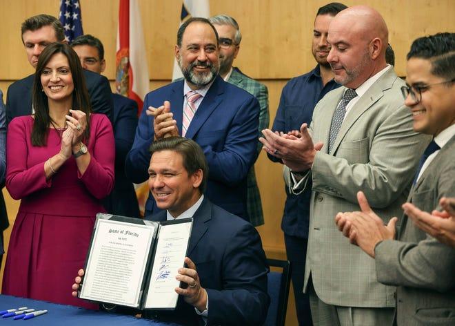 Florida Gov. Ron DeSantis hold up the signed legislation that seeks to punish social media platforms that remove conservative ideas.