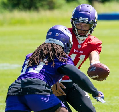 Minnesota Vikings quarterback Kellen Mond (11) hands the ball off to running back Dalvin Cook (33) in drills at OTA at TCO Performance Center on May 26.