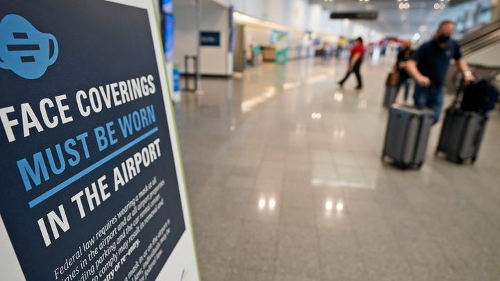 A sign requiring masks is displayed as travelers move about at Cleveland Hopkins International Airport on Wednesday.