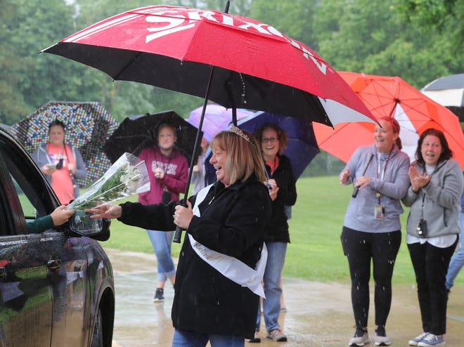 Riverview Elementary School teacher Kim Nixon gets a bouquet of flowers during a retirement parade in front of the school on Friday, May 28, 2021 in Stow, Ohio.  [Phil Masturzo/ Beacon Journal]