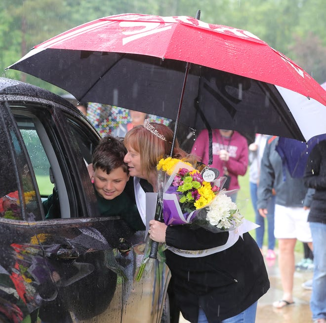 Riverview Elementary School teacher Kim Nixon gets a hug  and flowers from Braden Camp during a retirement parade in front of the school on Friday, May 28, 2021 in Stow, Ohio.  [Phil Masturzo/ Beacon Journal]