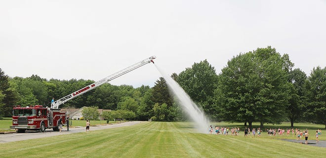 """ASHLAND As a reward, students in kindergarten through third grade at Edison Elementary School enjoyed some wet fun Thursday as they got sprayed by Ladder 15 from the Ashland Fire Department on a hot day in the low 70s. """"The kids love it and enjoy it,"""" said Kris Manley, who has been the principal for Edison School for the past six years."""