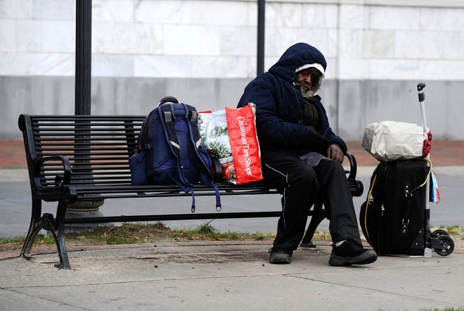 A homeless man sits on a bench at Augusta Common during frigid conditions in 2017. The Augusta Commission voted Tuesday to create a task force to address the city's homelessness problem.