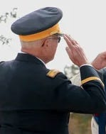 Retired Army Col. Tom Gray exchanges salutes with a World War II veteran during a ceremony last year at the Central Texas Veterans Memorial.