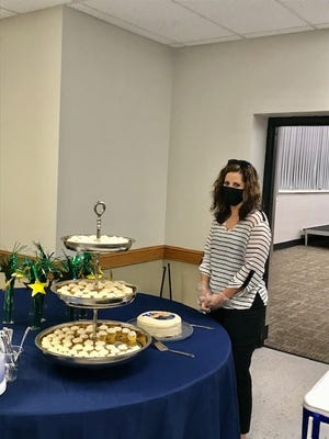 Board member Kelcey Peck assisting at the dessert table.