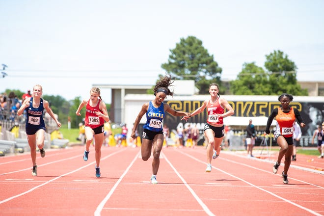 Circle's Kimalee Cook (middle) crosses the finish line in the Class 4A girls' 100-meter dash on Friday, May 28 at Wichita State's Cessna Stadium in the Class 4A state track and field meet.