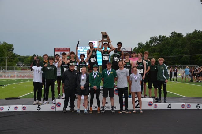 The Rock Bridge track and field team hoists the state championship trophy while posing for a photo Thursday in Jefferson City.