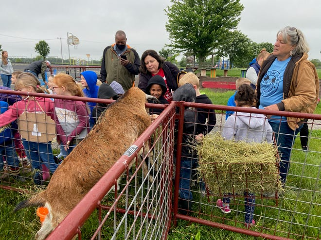 Laura Pierce, first grade teacher at Two Mile Prairie Elementary School, observes as her students interact with farm animals on Friday, with Linda DeShon with Four Oaks Farm on the right. The school held an agriculture day for students on Friday with several farm-focused stations.