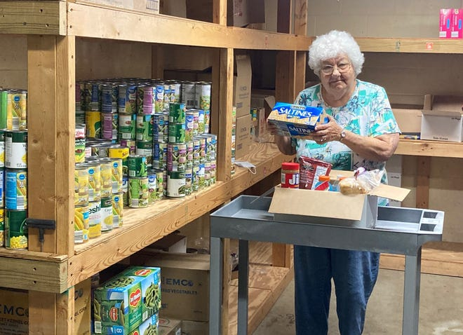 Rose Clemenson of The Salvation Army in Cambridge prepares a box of non-perishable food items and supplies that can be distributed to homeless individuals in Guernsey County.