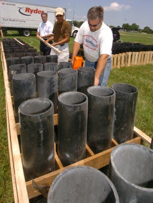 Frank Kuntz and Gil Ning give Chris Lindberg a hand setting up tubes for Wooster's annual fireworks display.