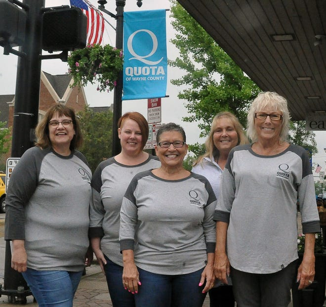 Quota of Wayne County members Julie Leathers-Stahl, Erin Foster, Sheri Boals, Brenda Cherry, and Tobin Spitler stand in front of their new rebranded Quota banner.