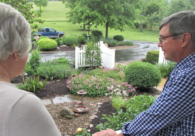 Kate and Dave look over their garden, one of the featured stops on the 2021 Holmes Garden Tour.