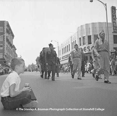 In this May 30, 1959, photo, Joseph P. Hogan, of 32 Clifford Ave., in Brockton, sits on Main Street and drinks a glass of tonic water as the Brockton Memorial Day Paradepasses by him.