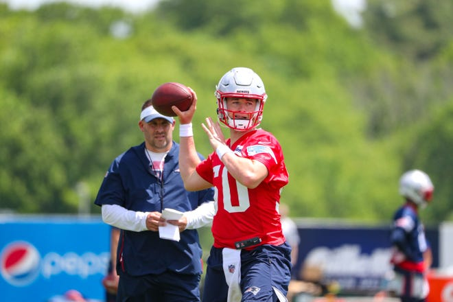 Rookie Mac Jones attempts a pass during Thursday's OTA session with offensive coordinator Josh McDaniels looking on.