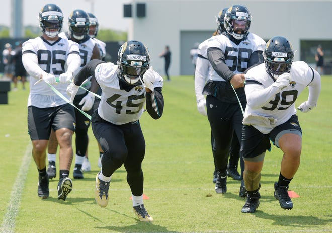 Jaguars defensive end K'Lavon Chaisson (45) and defensive tackle Daniel Ekuale (99 run drills while being held with elastic bands by teammates Roy Robertson-Harris (95) and Doug Costin (58) during Thursday's OTA session.