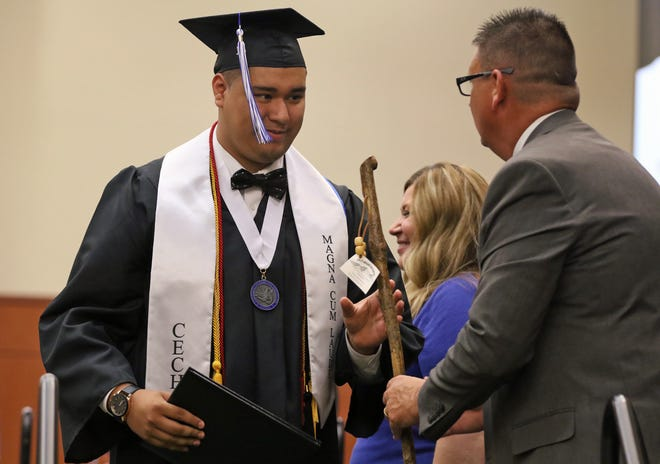 Cesareo Chavez Guerrero receives his diploma and his walking stick during the Cleveland Early College High School Commencement Thursday evening, May 27, 2021, at The LeGrand Center in Shelby.