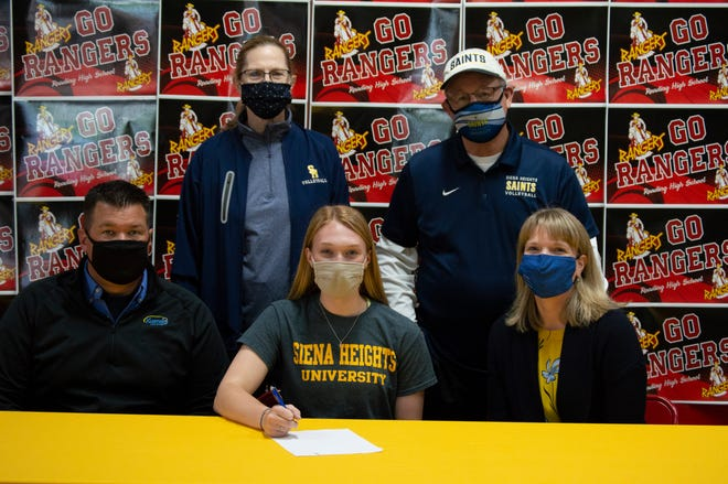 Claire VanDyke with her Family and Siena Heights University coaches.