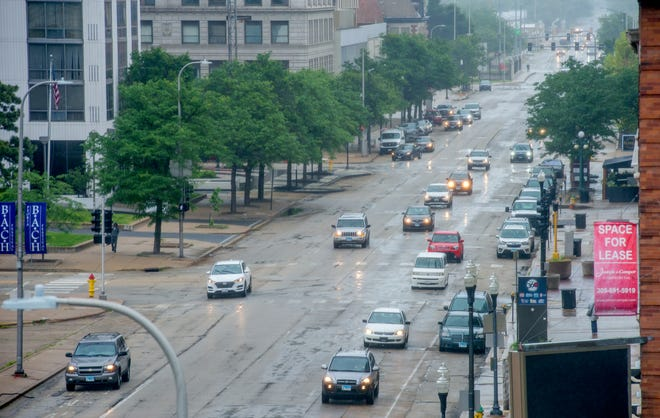 A line of vehicles travels down Southwest Jefferson Avenue through Downtown Peoria.