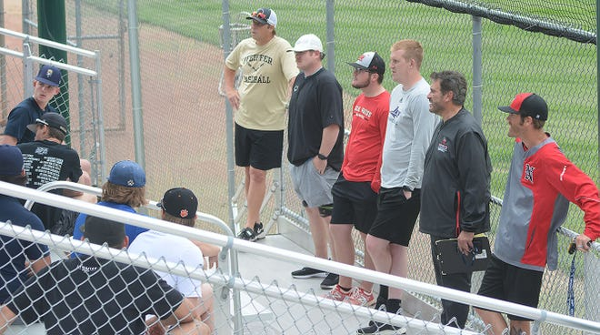 The coaches and staff of the Newton Rebels greet the team on the first day of practice.