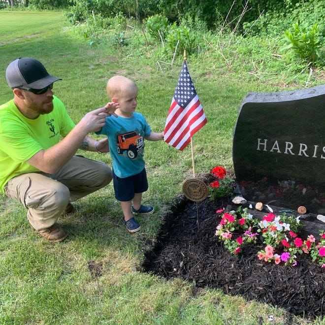 HOLDEN - Jon Harris, who works for the Holden Light Department, teaches his nephew Timothy Olson how to salute the American flag at the grave of U.S. Navy veteran Timothy A. Harris, Timmy's grandfather and Jon's father, at Grove Cemetery in Holden on May 27.