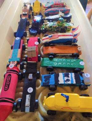 Vehicles line up for the Pinewood Derby at Lastella Field in Sterling on May 16.