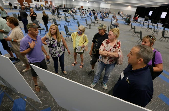At right, Airport Director Gene Conrad answers questions from the community at a workshop Thursday night for the public to voice their concerns about the environmental and noise impacts of an expansion to the Amazon Air Cargo facility at Lakeland Linder International Airport.  Special to the Ledger/ Calvin Knight
