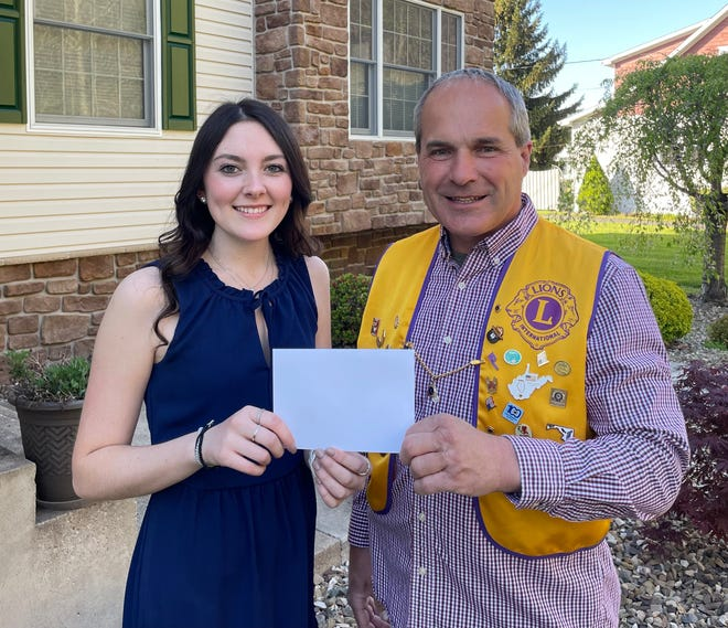 Sarah Sions, a Keyser High School Goldsworthy Scholar, presents a check to Joe Bane of the Keyser Lions Club to help ensure the program will continue.