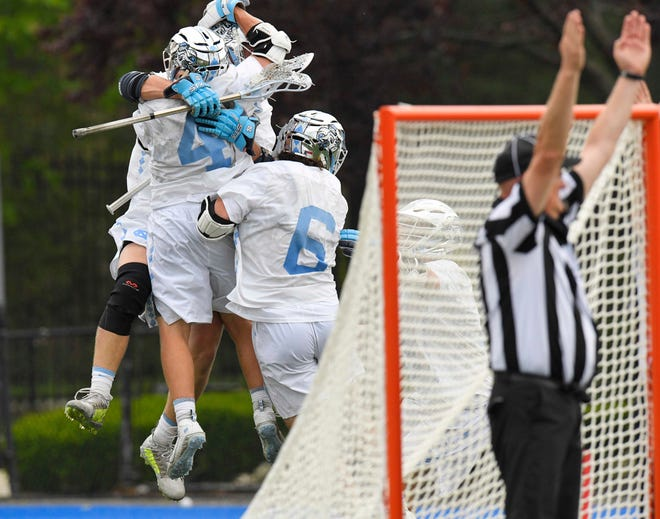 University of Carolina grad student Connor McCarthy (back) is mobbed by teammates after McCarthy scored the game-winning goal in the Tar Heels' 12-11 win in overtime in the quarterfinals of the NCAA Men's Lacrosse Championships on May 22 in Hempstead, New York.