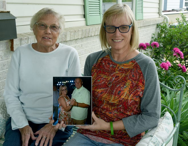 Susan Sass (right) and her mother-in-law, Kathleen Sass, hold a photograph of Susan dancing with her husband, Lt. Colonel Nicholas Sass of Newport. A lifelong Marine, he died of a stroke Thanksgiving morning. His interment will occur at Arlington National Cemetery in July.