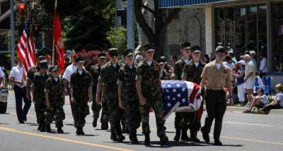 The Young Marines of Monroe County carry a flag-draped coffin in the 2017 Memorial Day through downtown Monroe to honor service members who have died for their country.