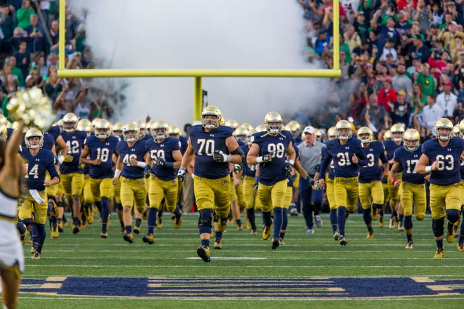 Notre Dame football players run onto the field before the 2017 game against Georgia in Notre Dame Stadium.
