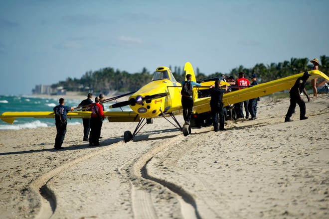 Palm Beach police and fire rescue personnel move a small airplane that made an emergency landing Friday afternoon on the beach in the 1400 block of North Ocean Boulevard in Palm Beach. The pilot was not injured.
