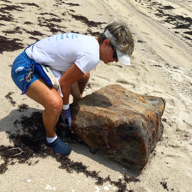 Diane Buhler, founder of the nonprofit Friends of Palm Beach, lifts a bale of rubber that washed up in Palm Beach in August 2020.