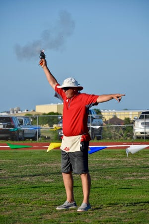 Ballinger High School athletic director and head football coach Chuck Lipsey fires off the starter's pistol to start one of the many track events during Ballinger ISD's Little Olympics on May 21.