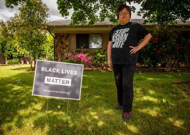 Xia Wang, 44, stands in front of her home in north Eugene where she's faced trouble over her Black Lives Matter signs. The sign pictured is her third sign — the first one stolen and the second defaced with spray paint. Wang wears a #StopAsianHate shirt which she got in Atlanta just days after the 2021 spa shootings which left eight people dead, six of which were Asian women.