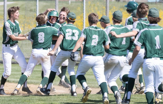 The Central Catholic baseball team rushes out to celebrate with Ethan Lyke (wearing helmet) after his walk-off single defeated Elyria Catholic 3-2 during Thursday's Division III district final at Norwayne High School. May 27, 2021.