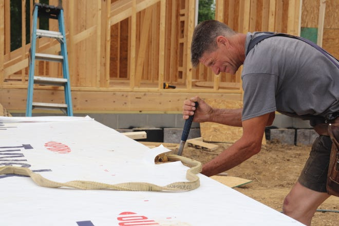 A worker prepares to raise a wall on a ranch-style home under construction in Louisville
