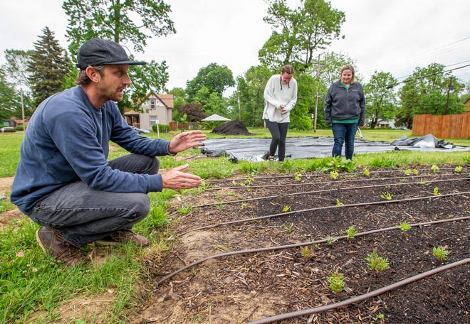 South Bend resident Tim Bayer describes the upgrades at the El Campito Child Development Center community farm as two center directors, Shannon Weyer, left, and Emily Hernandez, look on.
