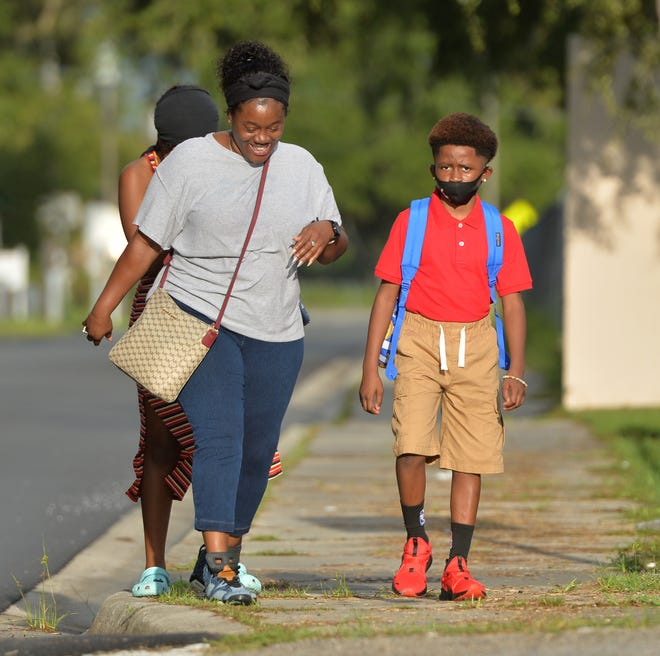 Samoset Elementary School 4th-grader Daylen Waiters, 10, walks to school Monday morning with his mom, Crystal Hicks, and sister, Paris Moreland, on the first day of class for students in Manatee County. [Herald-Tribune staff photo / Mike Lang]